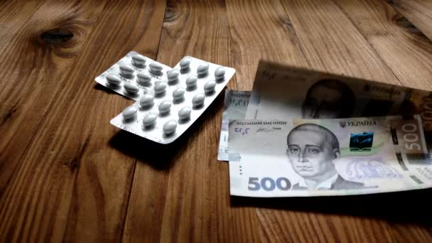 Ten člověk odpočítává určité množství peněz v ukrajinské měně a bere od stolu balíček pilulek. Koncept nákupu léčivých přípravků k léčbě.