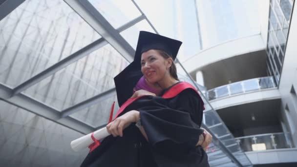 Šťastní absolventi objímají s diplomy v rukou