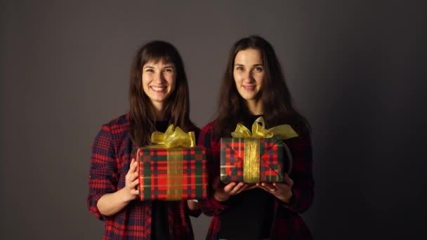 Usmívající se dvojčata držící dárkové krabice.