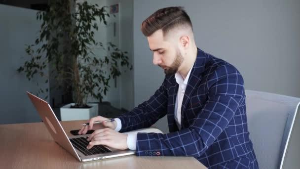 Profesionální obchodní muž sedí na své ploše v Office Studio pracuje na psaní na notebooku poznámky. Mladý muž Profesionální pomocí počítače sedí na svém pracovišti. Pracovník na volné noze.
