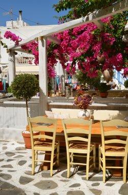 Restaurant under flowering trees in street of Chora Mykonos