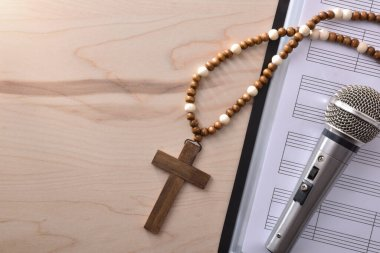 Conceptual detail of Christian religious music with mic on sheet music book and cross background close up. Top view. Horizontal composition.