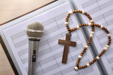 Conceptual detail of Christian religious music with mic on sheet music book and cross close up. Top view. Horizontal composition.