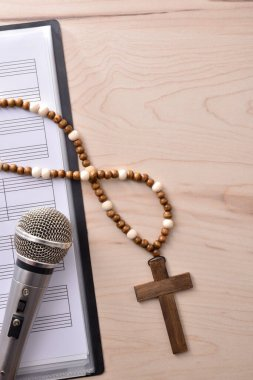 Vertical detail of Christian religious music with mic on sheet music book and cross background close up. Top view. Vertical composition.
