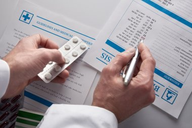 Doctor prescribing drugs and showing blood test report top view