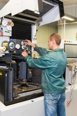 Worker operating industrial cnc machine in workshop.