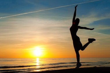 Enjoying the summer evening. Cheerful woman silhouette dancing o