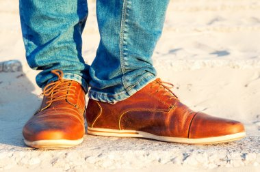 Mens legs in jeans and brown leather elegant  luxury shoes.