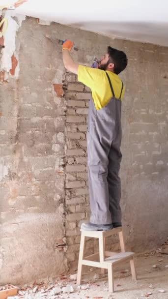 Junger Bauarbeiter zertrümmert Hauswand mit Hammer und Meißel.