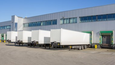 Trailers at docking stations of a distribution center waiting to be loaded