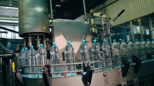 Innenraum einer Getränkefabrik. Förderband mit Wasserflaschen aus Kunststoff