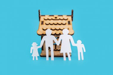 silhouette of a family and a wooden house on a blue background.