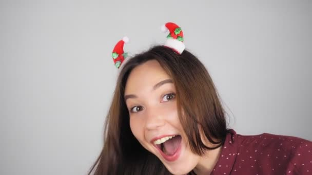 Happy woman with Christmas decoration in her hair. The woman is looking at the camera and smiling. Light background.