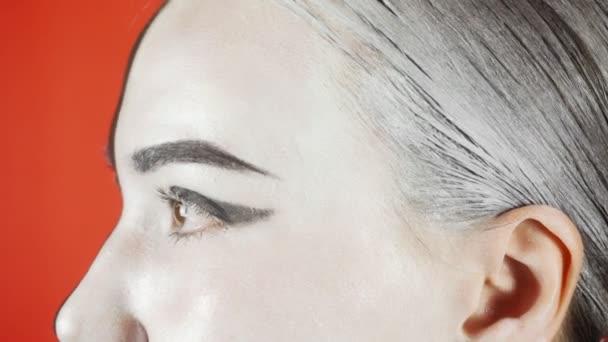 Mladá žena s černobílým make-upem se dívá do kamery. Jasné barevné pozadí. . Vysoce kvalitní 4K záběry