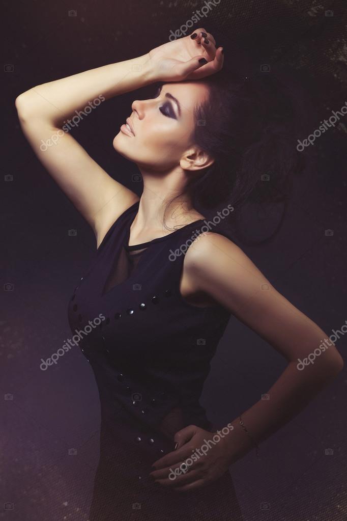 7027e5d6d537 Ragazza in vestito nero su una priorità bassa. Donne di bellezza. Gioielli  e bellezza. pelle perfetta
