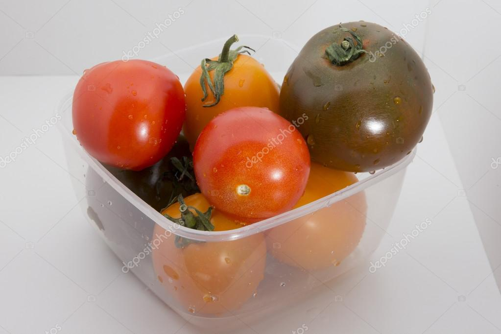 Tomatoes in a plastic food storage container Stock Photo