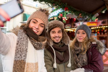 Couple, man, woman, friends have fun at the Christmas Market