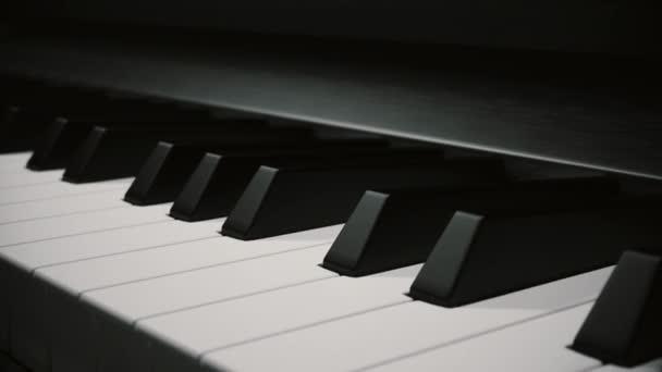 Hnutí z pohledu podél růže nad klávesy klavíru