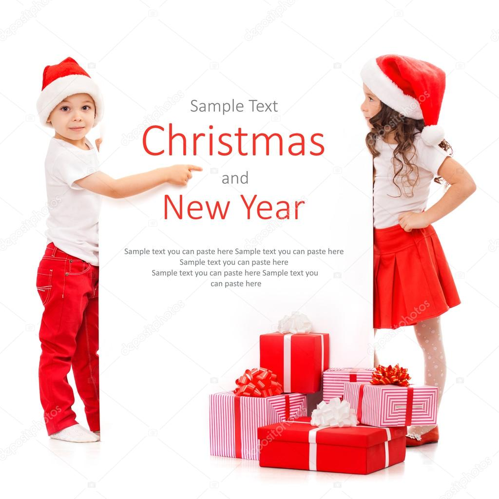 Happy little kids in Santa hat peeking from behind blank sign billboard