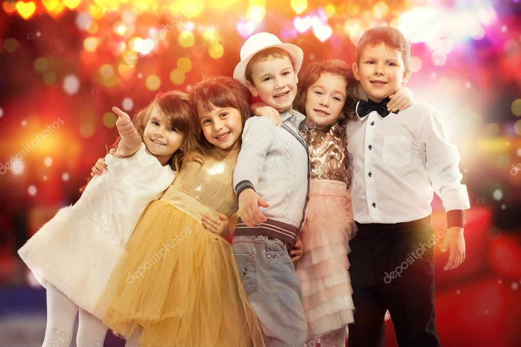 Group of happy kids with colorful lights on background.