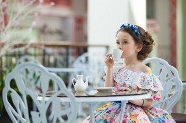 Portrait of little girl in a floral dress drinking tea