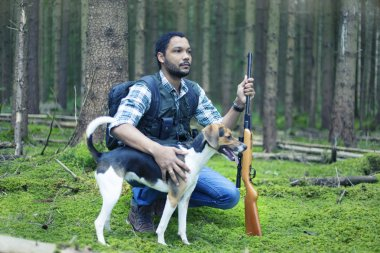 Interracial hunter in the forest with hunting dog