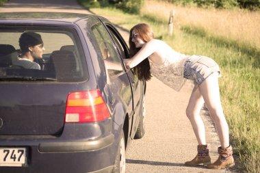 Sexy redhead woman hitchhiking