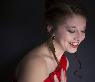Pretty teenage girl laughing and wearing red prom dress