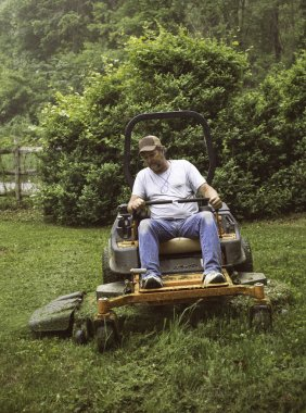 Man cutting grass on lawnmower