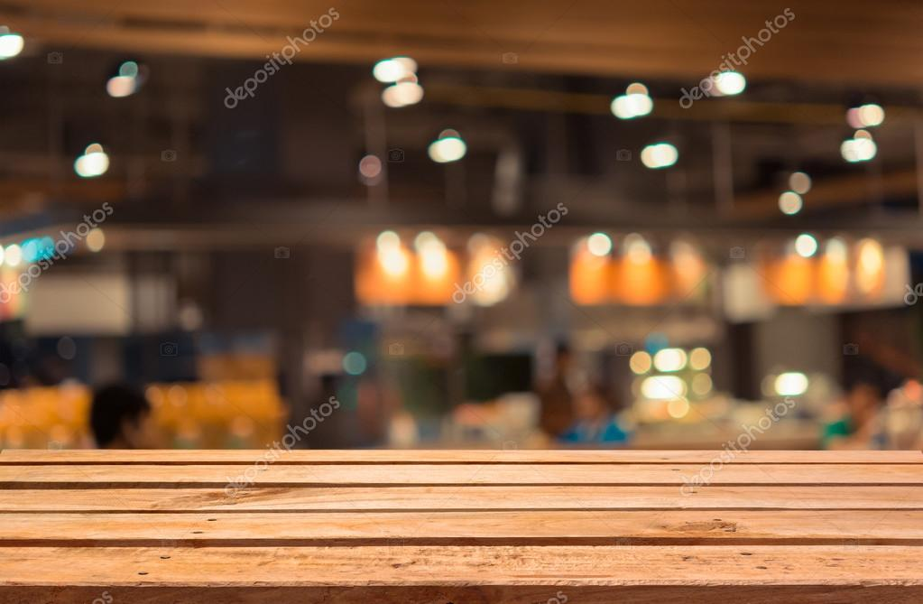 Empty wooden deck table on blurred food court background for Table background