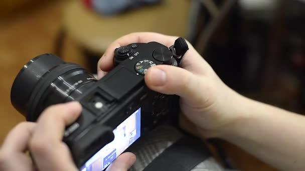 Vor dem Dreh stellt sie die Kamera auf. Mann dreht die Räder der Kameraeinstellungen und drückt die Taste auf der Rückseite. Frau schaltet Kamera ein und aus. schiebt sie den eingebauten Blitz der Kameras.