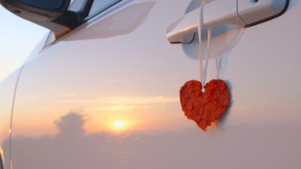 Krásné červené srdce visí na dveře zvládnout auta - fotoaparát pánve