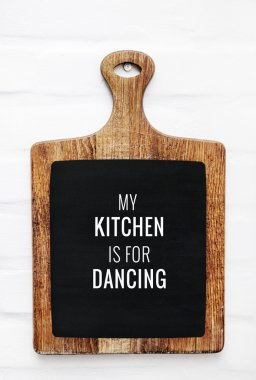 Quote MY KITCHEN IS FOR DANCING on the cutting board. Rustic style kitchen