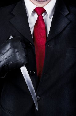 Man in black suit and black leather gloves holding knife, close up. stock vector