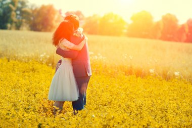 Just married couple hugging in the meadow