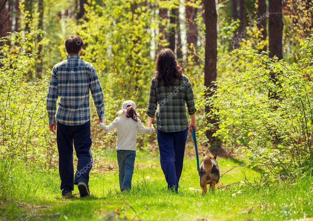 Family with dog walking in the forest