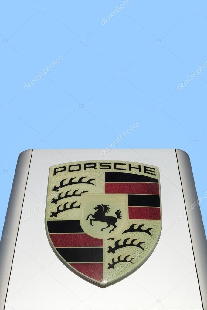 Porsche logo in front of a car dealer