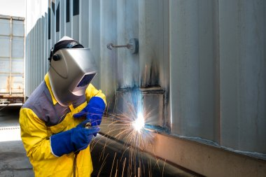 Industry worker with welding steel to repair container structure