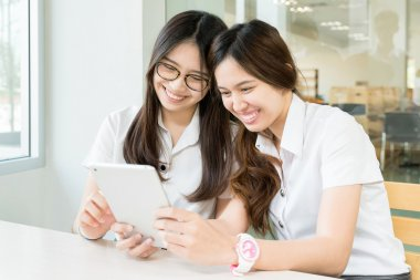 Two student with uniform in classroom with electronic tablet
