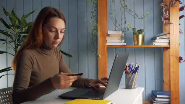 Woman sit at desk using credit card and laptop make on-line e-payment quick instant money transaction through internet services, pay bills, secure payment, economy safe money concept