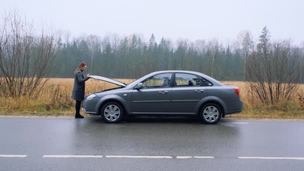 A young woman a broken car and opens the hood. The car suddenly broke down on a country road down while driving.