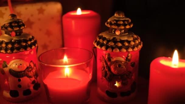 Weihnachten Hintergrund mit Geschenkbox und Dekorationen. Weihnachts- und Neujahrsdekoration. Weihnachtsdekoration mit Kerze. Kerzenschein gegen Weihnachtsdeko