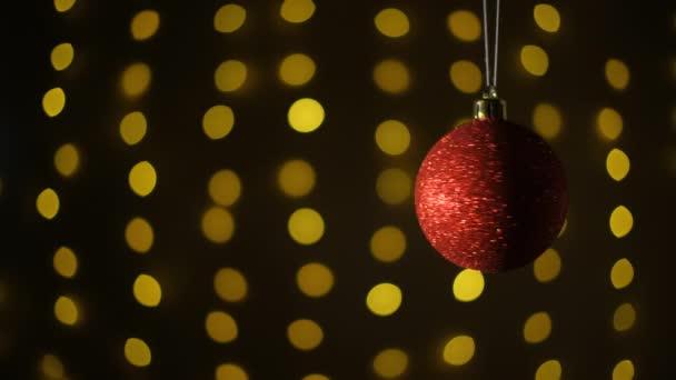 Krásná červená koule. Nový rok a vánoční ozdoby. Zářící girlandy. Rozmazané pozadí.