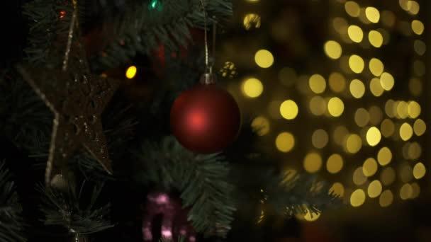 Karácsonyfa golyókkal a háttérben fényes ünnepi fények.