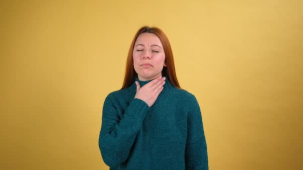 Young woman suffering from sore throat, breathing hard rubbing neck, respiratory infection with larynx inflammation, flu symptoms, tonsillitis or thyroid disorders. Shot isolated on yellow background