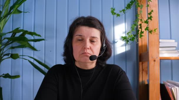 Stará žena ve sluchátkách s mikrofonem vedení on-line setkání konverzace, studovat vzdáleně nebo diskutovat o projektu s kolegy.