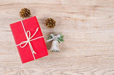 Gift box on wooden background. Red present with ribbon and christmas decoration.