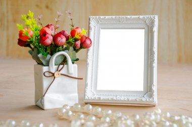 Flowers vase and blank white picture frame on wooden