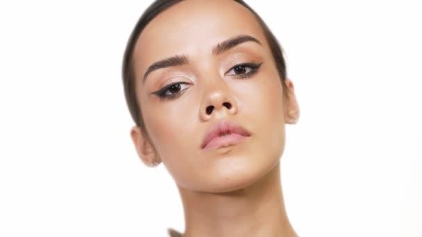 Roztomilá brunetka s hnědýma očima ukazuje velký make-up na bílém pozadí