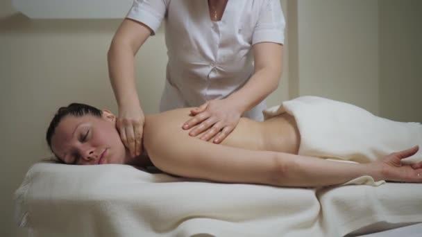 Krásná brunetka žena na krku masáž procedura v lázeňském salonu.